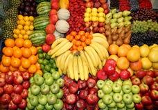 upp av många färgrika frukter på marknadsställning Arkivbilder