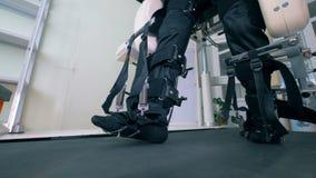 Slut upp av manben fixated med bälten som promenerar det rinnande spåret stock video