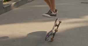 Slut upp av manben som skjuter skateboarden och utför trick på en stadsgata långsam rörelse arkivfilmer