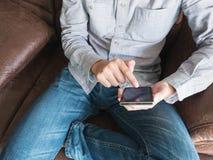 Slut upp av manfingerhandlaget till mobiltelefonskärmen Arkivfoton