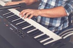 Slut upp av manhänder, medan spela på elektriskt piano Arkivfoto
