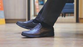 Slut upp av manlig fot som bär bruna nya modeskor Affärsmannen har shopping i skomarknad Arkivfoton