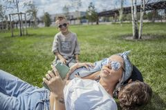 Slut upp av mumen och söner som ligger i parkera på grönt gräs lycklig begreppsfamilj royaltyfri fotografi