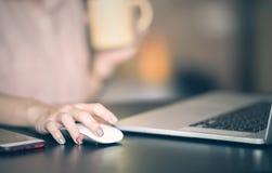 Slut upp av musen för för kvinnahandsökande och klick genom att använda bärbara datorn royaltyfria foton
