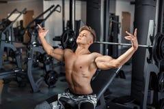 Slut upp av muskulösa lyftande vikter för en ung man i idrottshall på mörk bakgrund arkivfoto