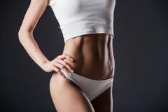 Slut upp av passformkvinnas torso med hennes händer på höfter Kvinnlign med den perfekta magen tränga sig in på svart bakgrund arkivbilder