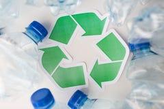 Slut upp av plast-flaskor och återvinningsymbolet Arkivfoto