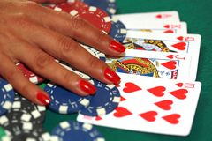 Slut upp av poker i handen för kvinna` som s spelar kort och chiper på gre royaltyfri foto
