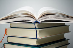 Slut upp av öppna boksidor på bunt av böcker Royaltyfri Bild