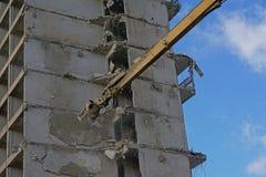 Slut upp av rivningkranen som ner bryter en gammal hyreshus Royaltyfri Bild