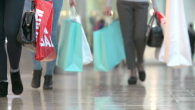 Slut upp av shoppares fot som bär påsar i shoppinggalleria arkivfilmer