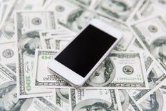 Slut upp av smartphonen och dollarpengar royaltyfri bild