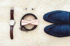 Slut upp av tillbehör för modern man Biege bowtie, läderskor, bälte, klocka, cufflinks, pengar och vigselringar Royaltyfri Bild