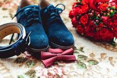 Slut upp av tillbehör för modern man Den körsbärsröda flugan, blått piskar den mest shoest och röda bröllopbuketten på en matta Royaltyfria Foton