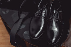 Slut upp av tillbehör för modern man svarta slips- och läderskor på den svarta glass tabellen Royaltyfria Foton