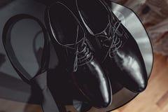 Slut upp av tillbehör för modern man svarta slips- och läderskor på den svarta glass tabellen Arkivfoto