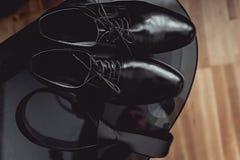 Slut upp av tillbehör för modern man svarta slips- och läderskor på den svarta glass tabellen Royaltyfri Foto