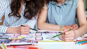 Slut upp av två kvinnaarkitekter som tillsammans diskuterar plan på skrivbordet med ritningar stock video