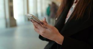 Slut upp av unga kvinnliga händer genom att använda telefonen, utomhus Royaltyfria Bilder