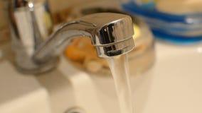 Slut upp av vattenklappet med rinnande vatten av och på på en badrumvask lager videofilmer