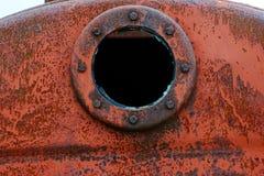 Slut upp bakgrund av den rostiga metallbehållaren med det rostiga runda hålet Arkivfoton