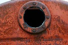 Slut upp bakgrund av den rostiga metallbehållaren med det rostiga runda hålet Royaltyfria Bilder