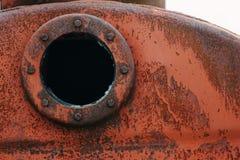 Slut upp bakgrund av den rostiga metallbehållaren med det rostiga runda hålet Arkivfoto