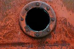 Slut upp bakgrund av den rostiga metallbehållaren med det rostiga runda hålet Fotografering för Bildbyråer