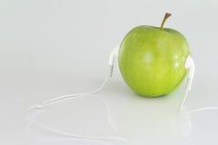 Slut upp begreppsmässiga gröna Apple med hörlurar med mikrofon Royaltyfri Fotografi