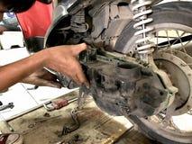 Slut upp bilmekanikern som reparerar motorcykeln Arkivbild