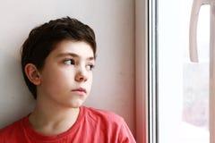 Slut upp blick för preteenpojkestående på fönstret arkivfoton