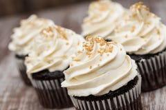 Slut upp chokladmuffin med vaniljglasyr på kaka Royaltyfri Bild