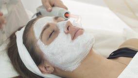Slut upp darsonvalizationflickaframsida med leramaskeringen i salong kosmetiskt tillvägagångssätt arkivfilmer