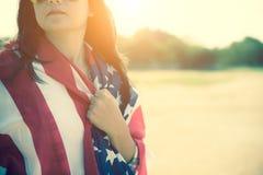 Slut upp den allvarliga framsidan för kvinna som täckas av USA flaggan Arkivfoton