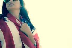 Slut upp den allvarliga framsidan för kvinna som täckas av USA flaggan Royaltyfri Bild