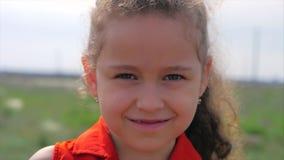 Slut upp den gulliga lyckliga caucasian lilla flickan f?r st?ende som ler se kameran som tycker om varm solig dag f?r sommarsemes stock video