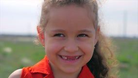 Slut upp den gulliga lyckliga caucasian lilla flickan f?r st?ende som ler se kameran som tycker om varm solig dag f?r sommarsemes arkivfilmer