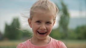 Slut upp den gulliga lyckliga caucasian lilla flickan f?r st?ende som ler se kameran som tycker om varm solig dag f?r sommarsemes lager videofilmer