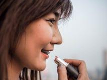 Slut upp den härliga asiatiska kvinnan som sätter makeupläppstift, lyckligt kvinnabegrepp som är filmiskt royaltyfri bild
