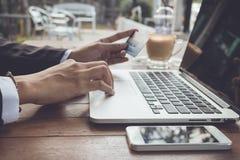 Slut upp den hållande kreditkorten för kvinnahand som direktanslutet betalas, och signal för bruksbärbar datortappning Fotografering för Bildbyråer