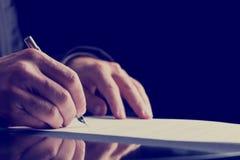 Slut upp den mänskliga handen som undertecknar på formellt papper royaltyfri foto