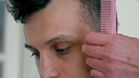 Slut upp den manliga framsidan i frisersalong Frisör Cuts Hair vid clipperen av den unga mannen lager videofilmer