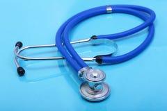 Slut upp den medicinska stetoskopet på blå bakgrund Arkivbilder