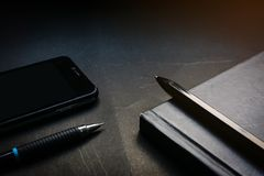 Slut upp den svarta anteckningsboken, penna, blyertspennan och mobiltelefonen på svart skrivbordbakgrund i dramatisk tändande sig royaltyfria bilder