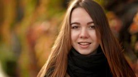 Slut upp den utomhus- kvinnaståenden Le unga flickan med långt hår Backlit av solen Bekläda beskådar stock video
