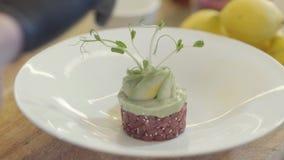Slut upp den vita stora plattan med att förbluffa garnering av en maträtt Rund form av den lilla cutted tonfiskfisken, överst grä lager videofilmer