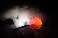 Slut upp det enkla förstoringsglaset med det svarta handtaget som lutar på trätabellen på orange röd rökmörkerbakgrund Overklig b Royaltyfri Foto