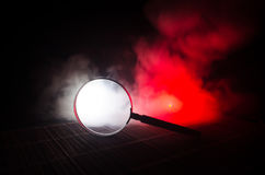 Slut upp det enkla förstoringsglaset med det svarta handtaget som lutar på trätabellen på orange röd rökmörkerbakgrund Overklig b Arkivfoton