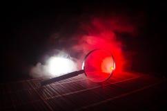 Slut upp det enkla förstoringsglaset med det svarta handtaget som lutar på trätabellen på orange röd rökmörkerbakgrund Overklig b Royaltyfria Foton