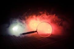 Slut upp det enkla förstoringsglaset med det svarta handtaget som lutar på trätabellen på orange röd rökmörkerbakgrund Overklig b Arkivbild